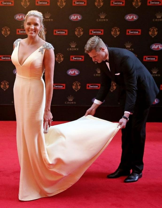 This picture of Nick tending to his wife's train on the Brownlow red carpet in 2017 is proof gentlemen still exist.