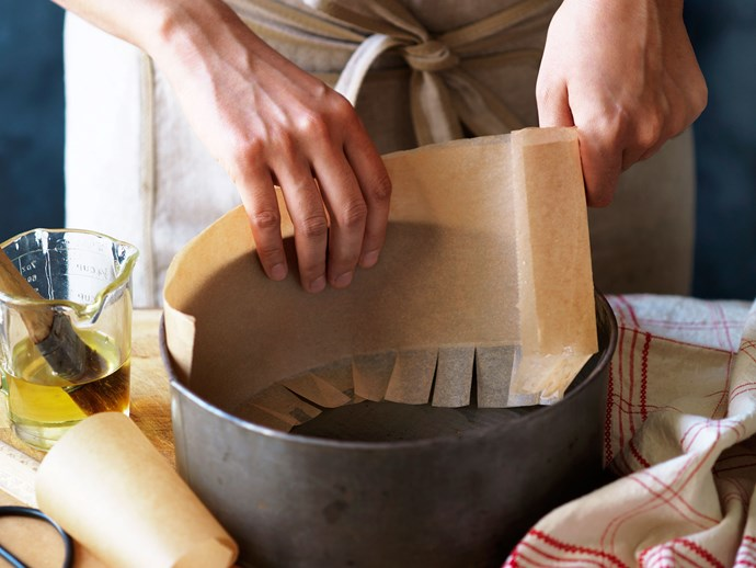Lightly grease the pan to hold the paper in place. Position the paper around the side of the pan, with the snipped fold at the bottom. Two or more layers of paper are often used.