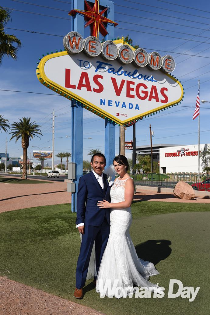 The happy couple pose in front of the landmark Vegas welcome sign.