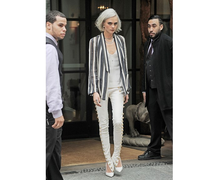 Cara Delevingne debuts a grey hair style this week in a Chanel outfit with button-down satin pants and a striped blazer.