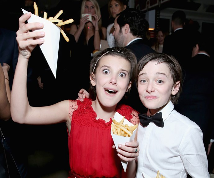 The kids from *Stranger Things* (Millie Bobby Brown and Noah Schnapp) look delighted with the food at a SAG Awards after party.