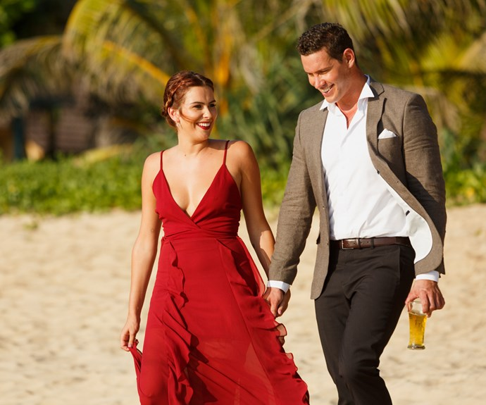 The pair take a romantic stroll on the beach before a rose ceremony in Thailand.