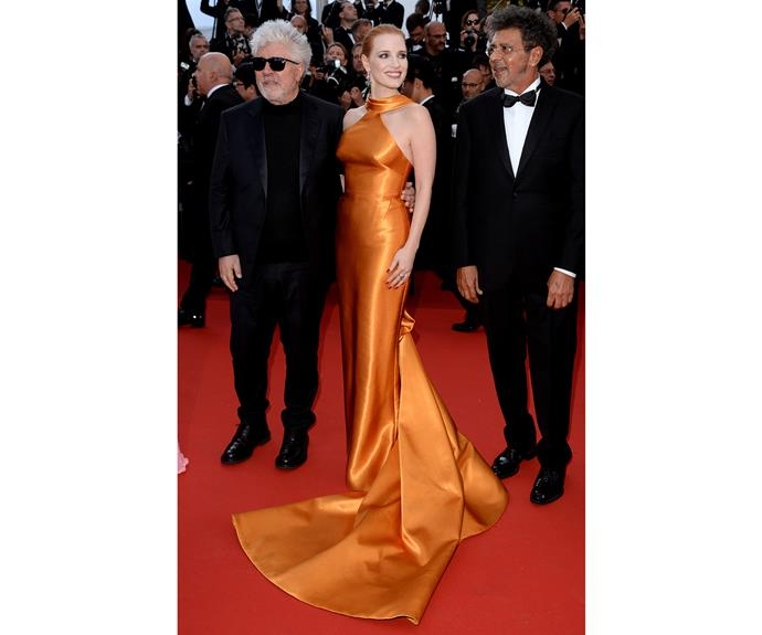 Jessica Chastain glows in a burnt orange Giorgio Armani Privé gown for the Cannes 70th Anniversary screening.