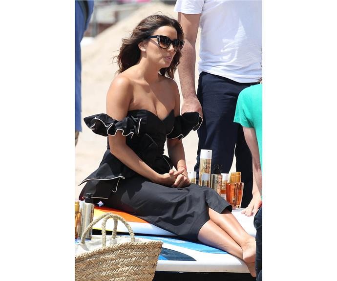 Eva Longoria relaxes at a beach club in an off-the-shoulder outfit.