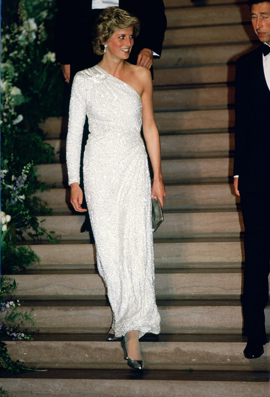 During her time in the royal family Princess Diana was also a fashion icon of the time. Here's her in an ivory Hachi gown during a gala dinner in Washington DC in November 1985. The one-shouldered silhouette was a favourite of hers. *(Image: Getty)*