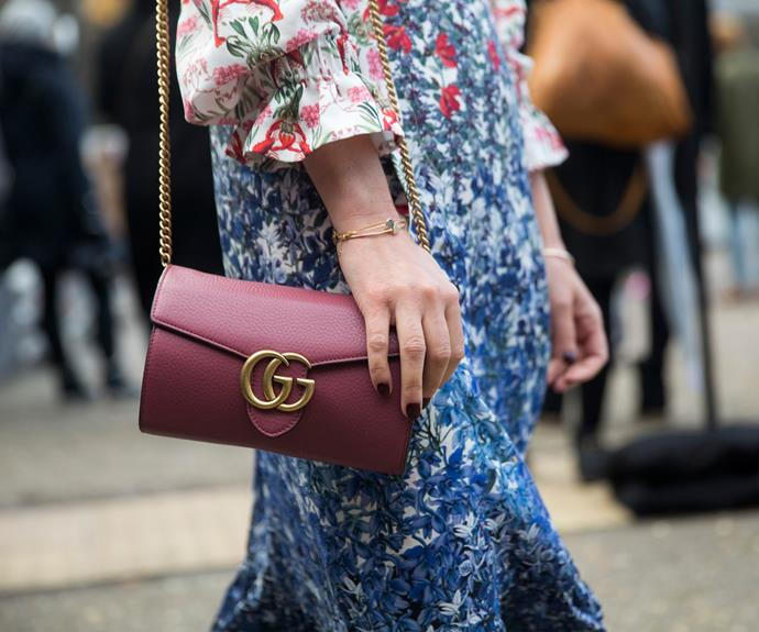 A London Fashion Week guest wears a vintage rose leather Gucci GG Marmont chain bag over a floral dress.