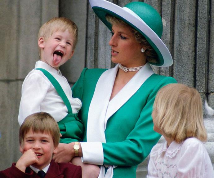 A cheeky Prince Harry plays up for the crowds while his doting mother looks on.