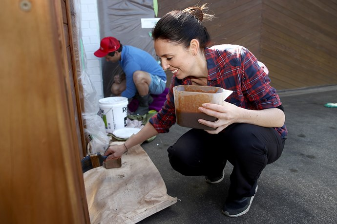Jacinda Ardern and partner Clarke Gayford  varnishing a fence at their home in Point Chevalier, Auckland.