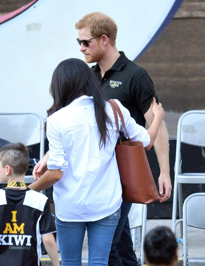 Meghan's hand on Harry's arm indicates the couple's closeness.