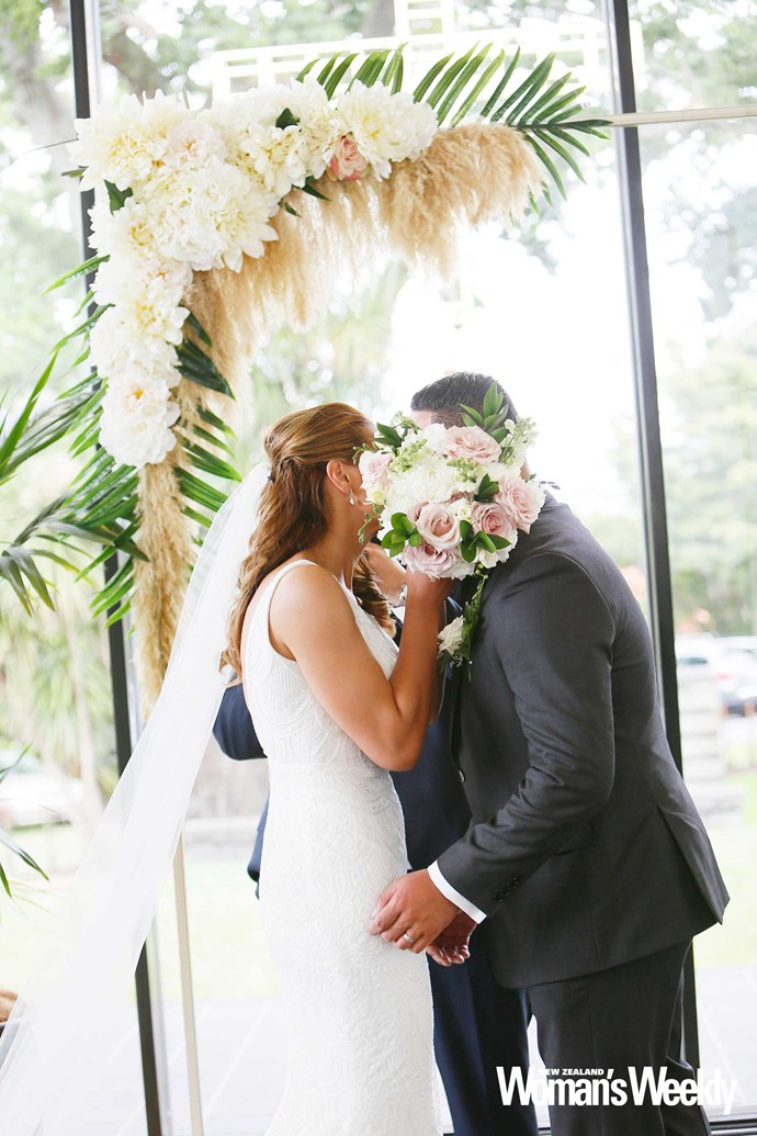 Nothing to see here! Grace hides the couple's first kiss as newlyweds with her bridal bouquet.