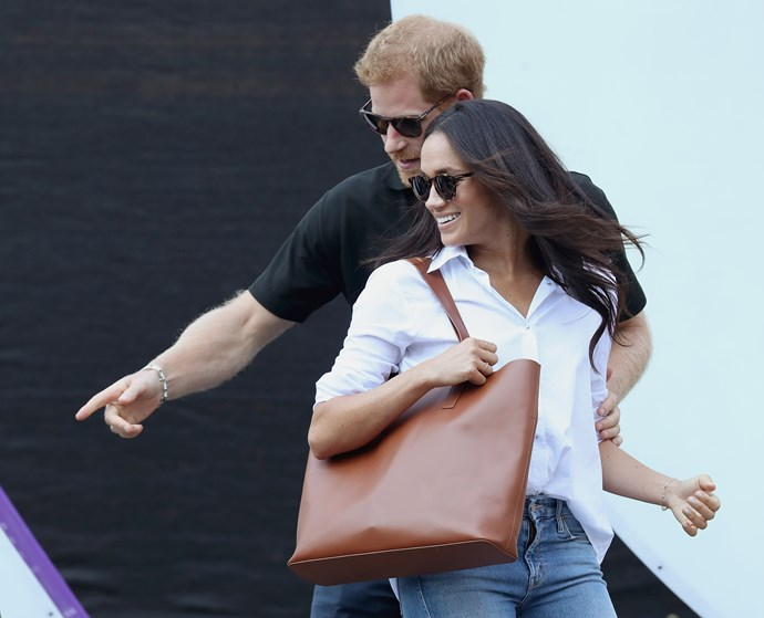 Prince Harry keeps a protective hand on Meghan's arm during their first public outing at the Invictus Games.
