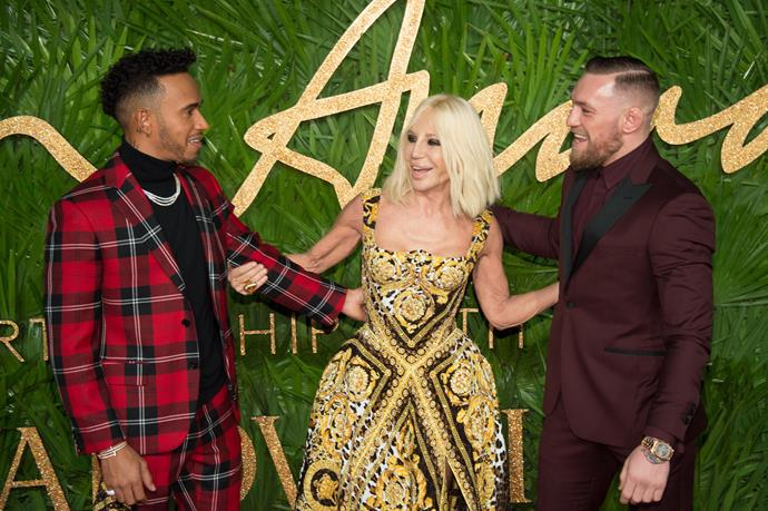 It's a Donatella Versace sandwich with Lewis Hamilton to the left and Conor McGregor to the right, all wearing Versace.
