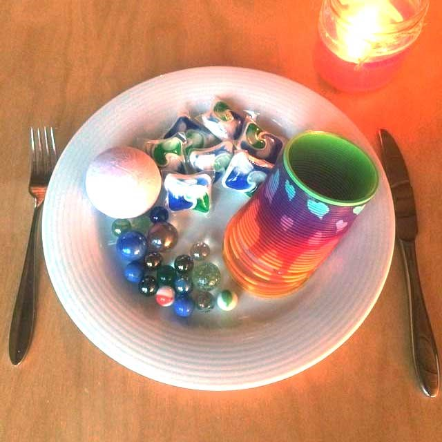 A meme depicting marbles, a bath bomb, a slinky and laundry pods as a dinner.