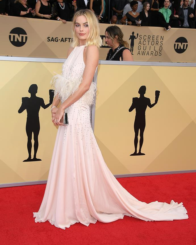 **Screen Actors Guild Awards (SAG)**  Margot deserves an award for this look alone! She wears a gorgeous feather featured Miu Miu gown and pairs it with flawless make-up. Her loose curled blunt bob makes us want to chop our locks just like it!