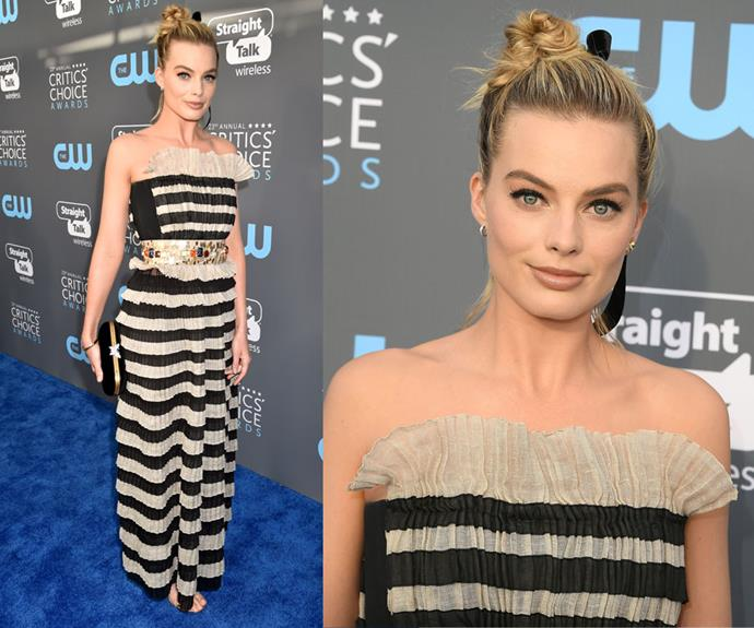 **The 23rd Annual Critics Choice Awards**  Margot opted for something a bit out of the ordinary with this Chanel striped gown and embellished belt look waist. She paired the busy look with a simple top knot and natural lip. This edgy ensemble pushed the limits on standard red carpet attire and she rocked it.