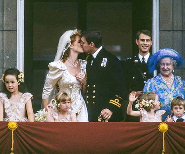 Prince Andrew and Sarah Ferguson seal their marriage with a kiss on the balcony on July 23, 1986. *(Image: Getty)*