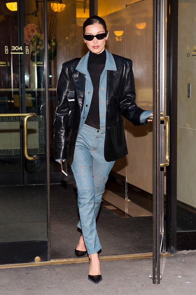 **Bella Hadid** pairs her denim on denim ensemble with a black turtle neck and black leather jacket.
