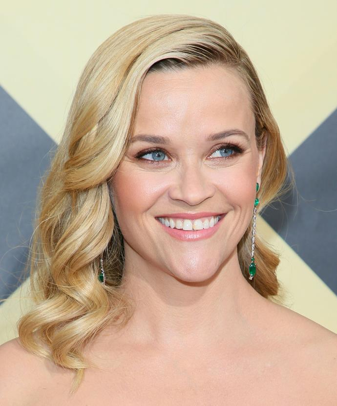 Reese Witherspoon's side part, large curls and peach make-up is a great wedding day look for the romantic bride. Credit: *Getty Images*
