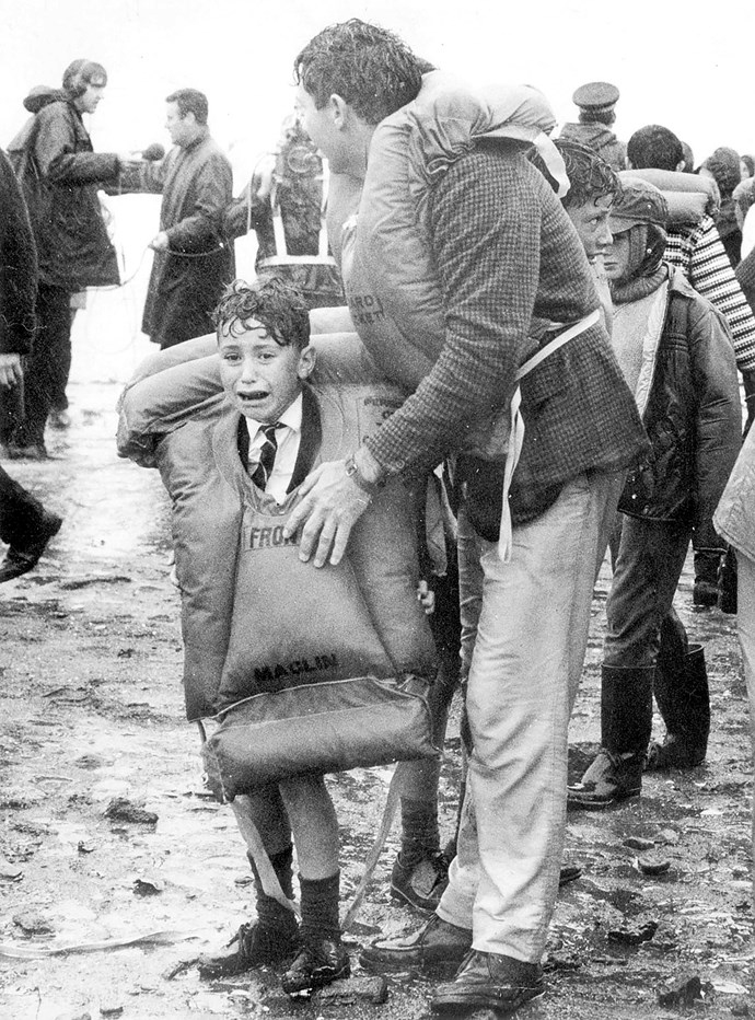 Young survivor Joe O'Neill (son of Clarence and Lydia O'Neill) stands frightened, wet and cold in his adult-sized lifejacket after safely making it ashore.