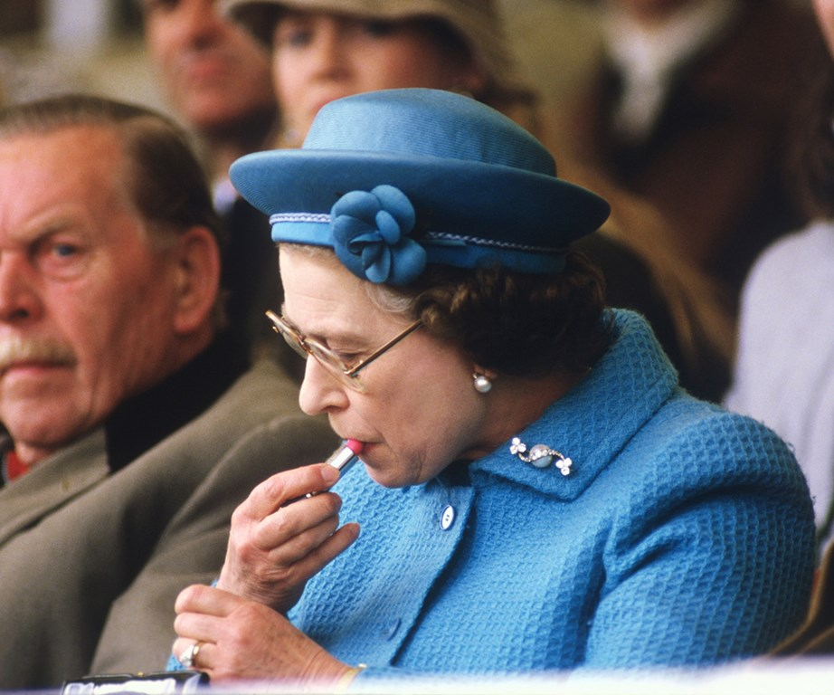 The Queen is often seen touching up her lipstick - Clarins and Elizabeth Arden are said to be her favourites. *(Image: Getty)*