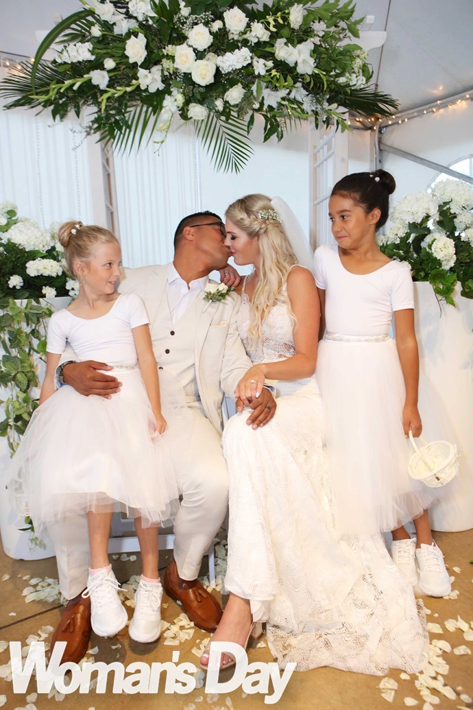 Their girls look on as their parents seal their new union with a kiss.