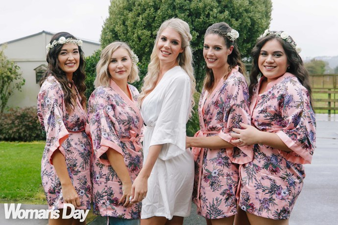 The bridesmaids wear white flowers in their hair, which reflect the romantic floral theme of the day.