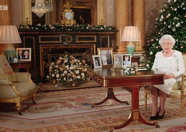 In the far left background, The Queen has a framed photo of Harry and Meghan next to a portrait of Prince Charles and Duchess Camilla.