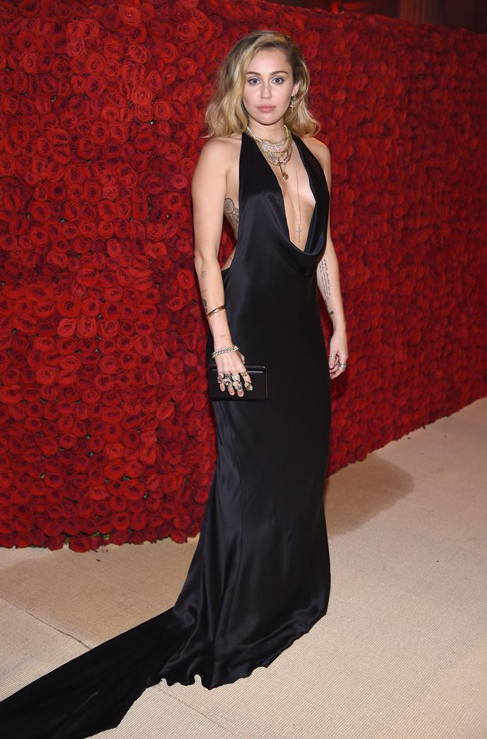 Miley Cyrus wows in this simple black plunging dress.