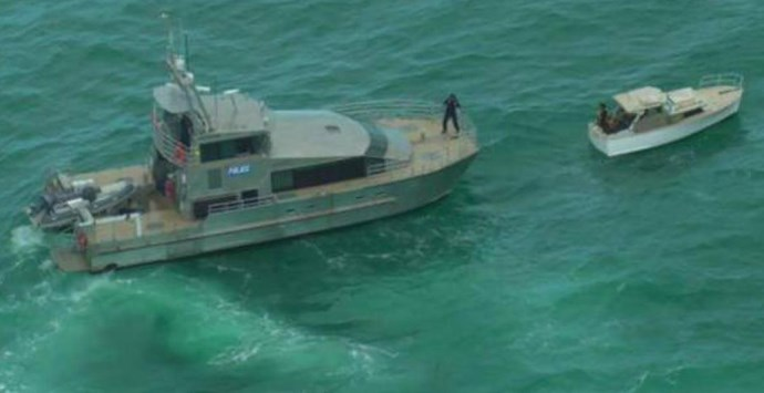 The police launch prepares to tow their boat to safety after they were finally found.