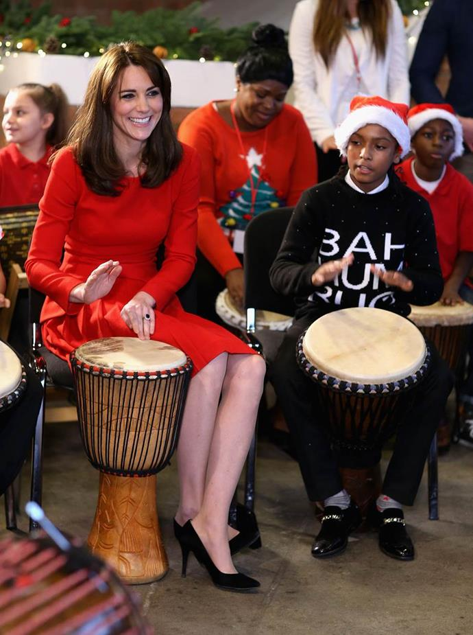 Kate takes part in some drumming 'music therapy' as she attends the Anna Freud Centre Family School Christmas Party at Anna Freud Centre on the 15 December, 2015 in London, England, in the same red Alexander McQueen number.