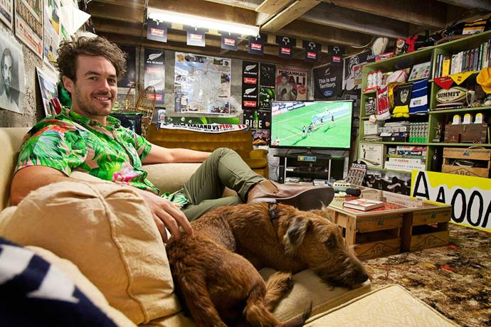 "Josh Hickford in his ""man cave"" with his dog, Cedric."