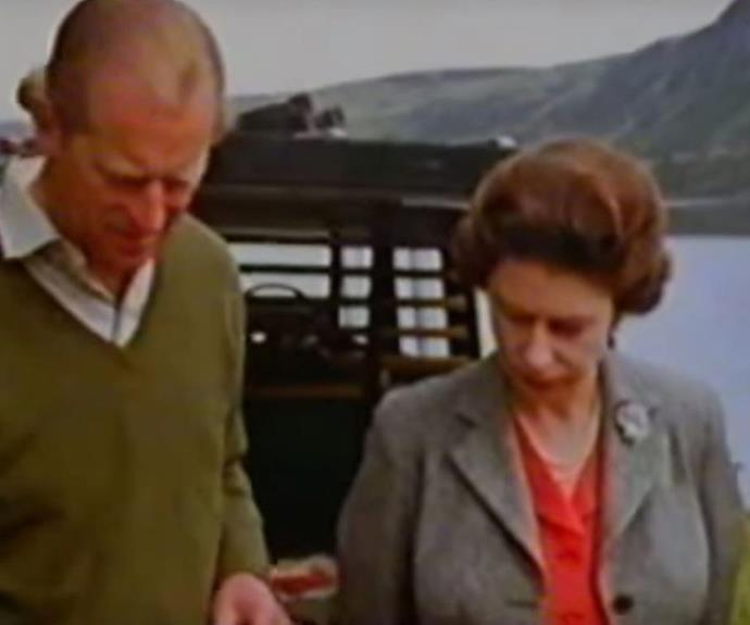Domestic bliss! The Queen watches on as her husband Prince Philip turns the sausages on the barbeque.