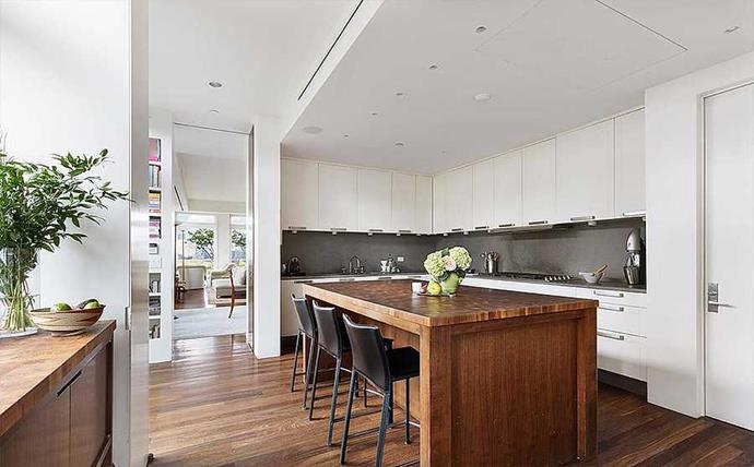 The minimalist kitchen is centered around a wooden island with a butcher block top.