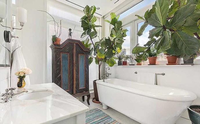 But it's the master bathroom that's a Pinterest dream. We love the roll top tub, marble sink and jungle of plants.