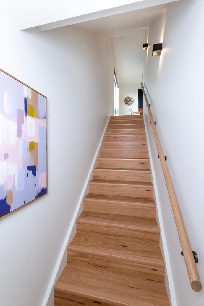 A pastel, abstract artwork sits at the bottom of the staircase leading up to Amy and Stu's kitchen, living and dining space.