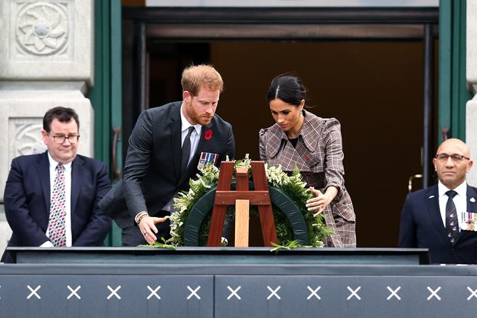 The pair lay a wreath out of respect.