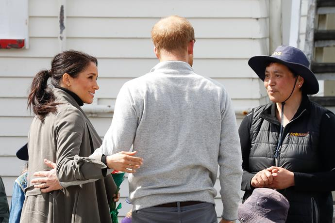 Ever the tactile couple Prince Harry and Duchess Meghan have each other's back as they stop to chat with fans while walking to Maranui Café in Wellington.