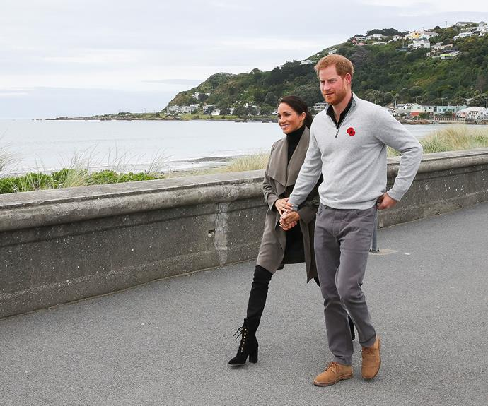 Prince Harry and Duchess Meghan hold hands as they walk along Lyall Bay to visit Maranui Café  in Wellington.
