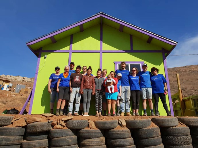 Art and the rest of the Volunteer Build team proudly stand outside the home they built - along with the new homeowners. *Photo: Emily Hlavac Green*