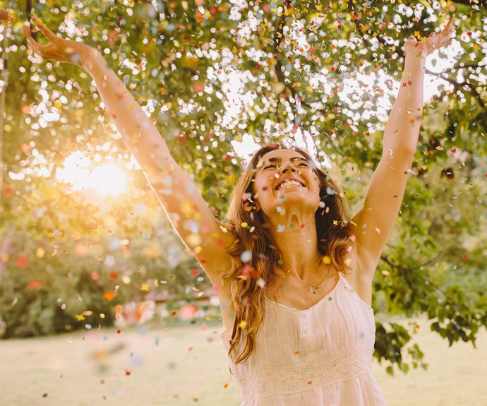 Happy woman throwing arms up in confetti