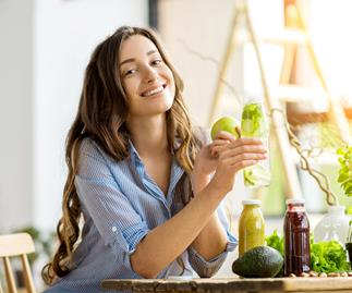 Happy woman sits at table with green vegetables and juices