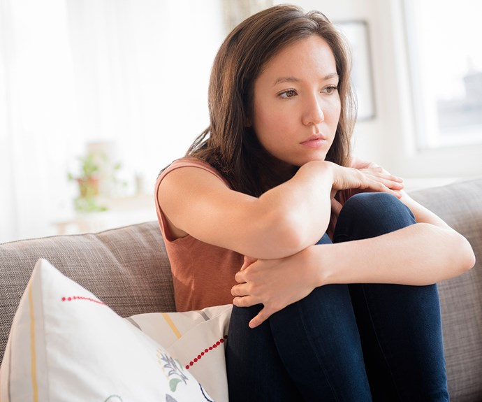 Woman looking sad on couch alone