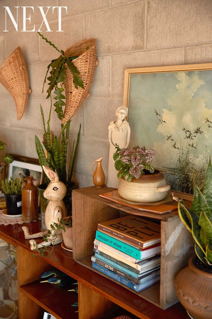 The wall unit in the dining room is full of whimsical knick-knacks and plants.