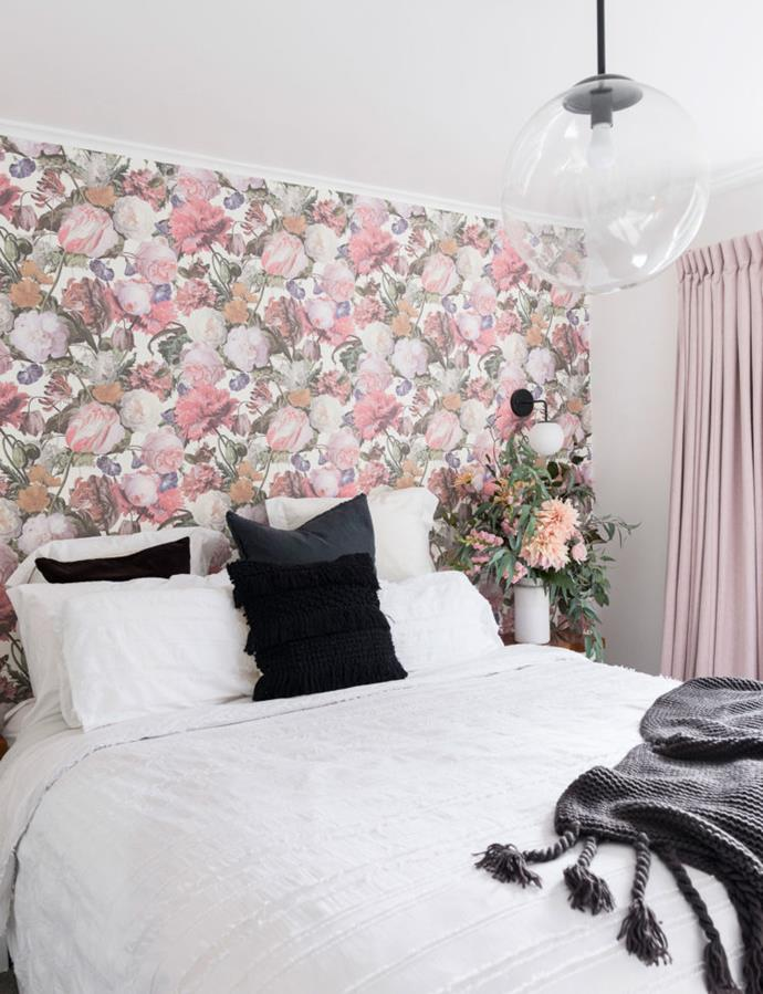 The romance of the Eijffinger wallpaper and blush drapes is tempered by modern black accents in the bedroom.