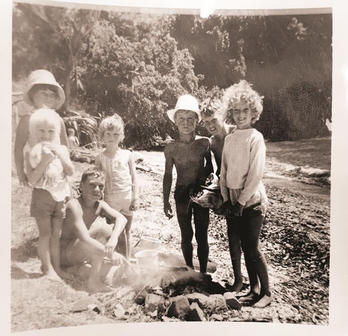 "**Dame Trelise Cooper, designer**  ""This photo was taken in the mid-1960s, when I was about nine years old. We were on the beach in front of our beautiful waterfront family bach at Scandrett Regional Park. We went there most weekends and Christmases for 35 years. This was a typical day with my siblings and our family friends – building a fire and cooking oysters, pipi, crabs and mussels. I'm on the far right – with the curls, of course!"""
