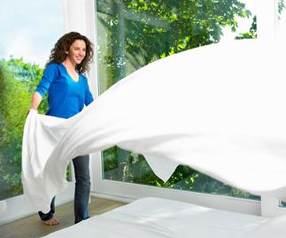 Woman making a bed on a crisp sunny day
