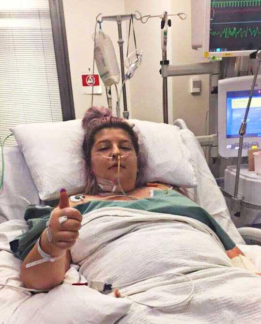 Seizures  and carrying excess fluid, Chanelle gives a thumbs-up from her hospital bed.