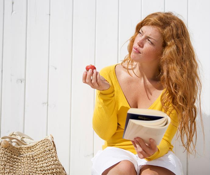 Red head young woman sitting on bench reading a book and eating a strawberry thoughful