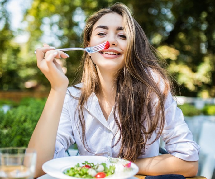 Happy young woman eats a salad in the sun