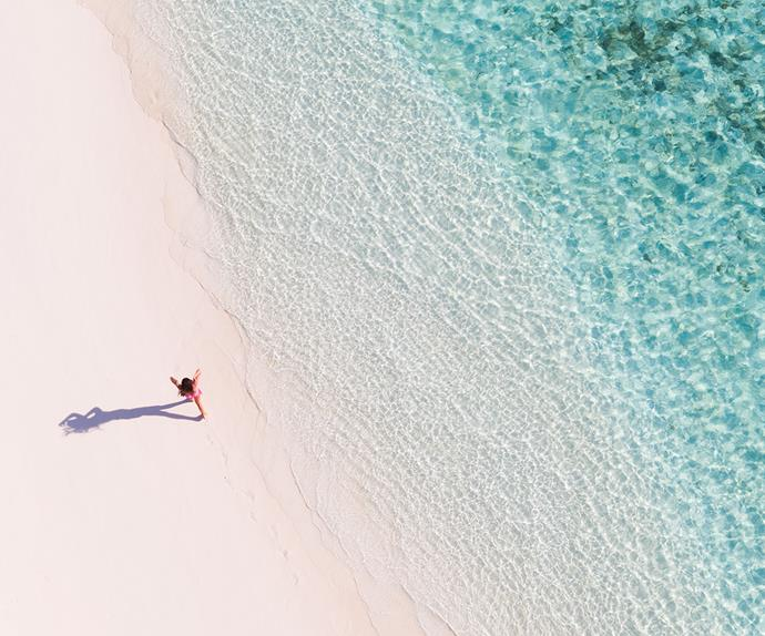 woman walking on a beach, birdseye shot